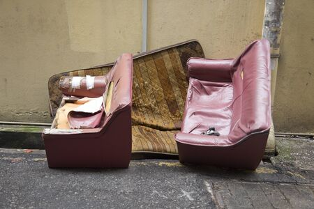 Discarded furniture and mattress by roadside in Asian city Stock Photo