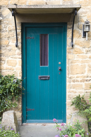 overhang: Aqua blue painted door of an english stone built cottage with overhang