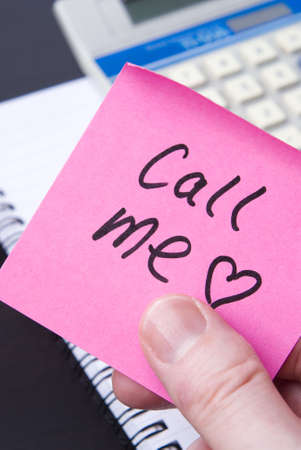 office romance: Pink postit note left with calculator and spiral notebook on office desk. Concept for office romance and St Valentines Day. Stock Photo