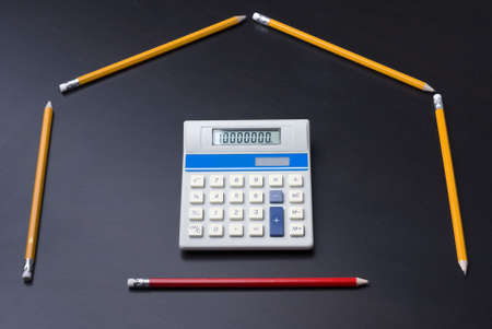 Pencils as house with calculator door as a business, finance, mortgage concept. 10,000,000 on calculator. Standard-Bild
