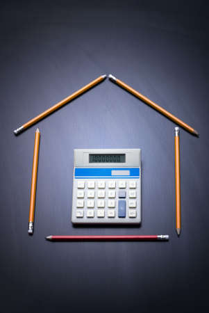 Pencils as house with calculator door. Desk as background. Copy space. Business and house finance concept. 10,000,000 on calculator.