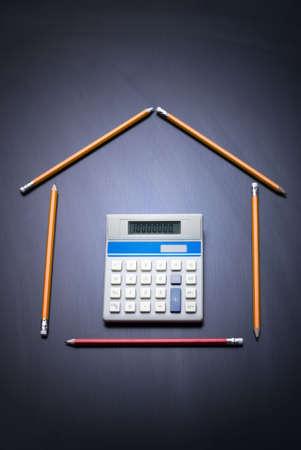 L�pices como puerta de casa con la calculadora. Escritorio como fondo. Copiar el espacio. Negocios y finanzas concepto casa. 10.000.000 en la calculadora. Foto de archivo