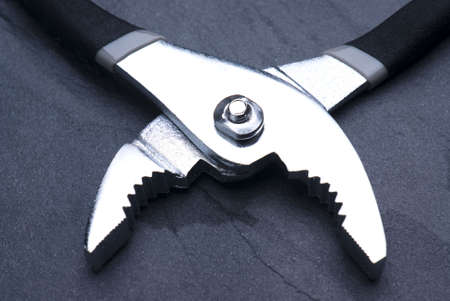 gleam: Pair of pliers shot to contrast chrome gleam against slate background Stock Photo