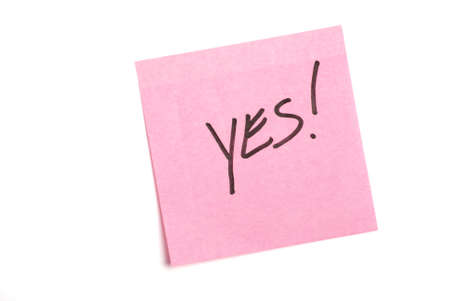 notelet: Pink post it note isolated on white with yes written.