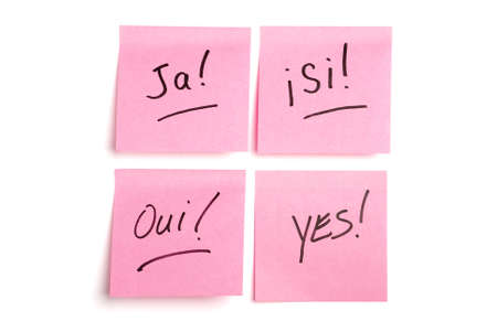 notelet: Pink post it notes isolated on white with ja, si, oui, and yes written