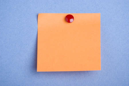 notelet: Post it note. Orange with red drawing pin. Isolated on blue background. Stock Photo