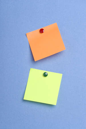 notelet: Two post it notes with drawing pins on blue background Stock Photo