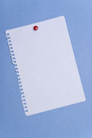 Blank torn spiral-bound notepaper page on blue Standard-Bild