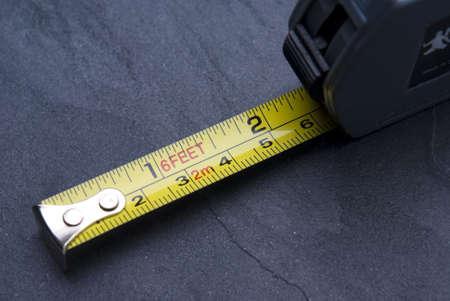 Medida de la cinta con las marcas imperiales y m�tricas en el fondo de pizarra.