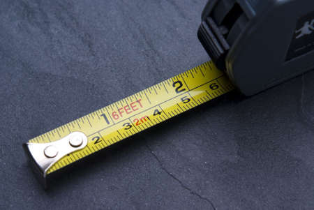 millimetre: Tape measure with imperial and metric markings on slate background.