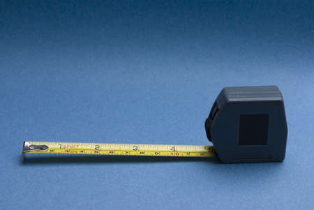 millimetre: Tape measure with imperial and metric markings on graduated blue background. Stock Photo