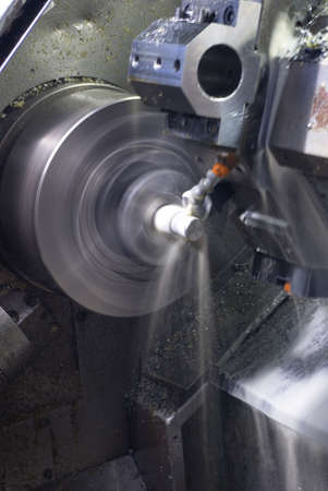 on the lathe: Long exposure of CNC lathe with cooling fluid on machined part