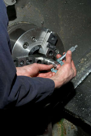 Hands measuring diameter of machined piece using a tool on CNC lathe