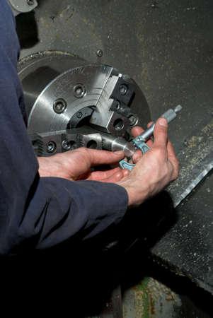 Manos de medici�n del di�metro de mecanizado pieza mediante una herramienta de Torno CNC