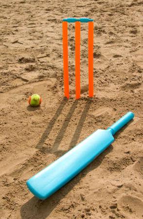 Bright orange toy cricket set on beach with shadow approaching viewer. Standard-Bild