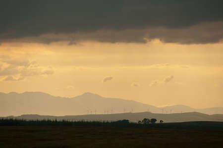 llegar tarde: Puesta del sol sobre las turbinas como nubes oscurecen. Podr�a ser el concepto para el clima de incertidumbre, preocupante futuro o dejando la mejora del medio ambiente demasiado tarde. Foto de archivo