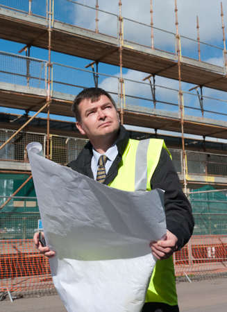Architect or engineer at work on a building site. Checking plans against the construction work. Confident gaze. Stock Photo - 7797257