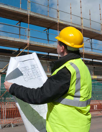Architect, foreman or engineer at work on a building site. He inspects the site while looking at the plans for the construction site.
