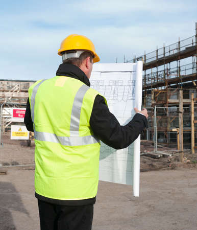 Architect or engineer at work on a building site. Checking plans against the construction work. Back to camera. Plans clearly visible. photo