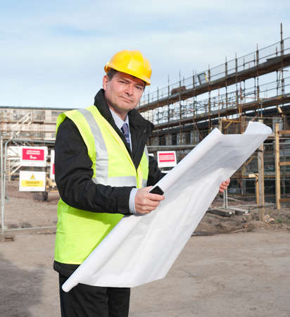 Architect or engineer at work on a building site. Holding plans for construction work. Confident gaze and smile at camera. Standard-Bild