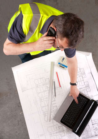 Builder on phone checks blueprint and uses laptop. Focus on face. Elevated view. photo