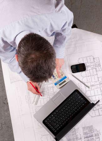 Arquitecto o ingeniero calcula y dibuja sobre el plan. Se centran en la mesa. Vista elevada.