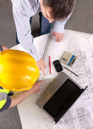 Vista elevada de arquitecto y constructor apuntando al plan. Centrarse en la sobremesa