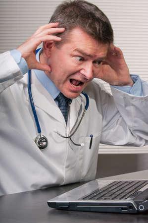 M�dico en escritorio en cirug�a consigui� la cabeza en el horror en la pantalla de la computadora port�til.  Foto de archivo