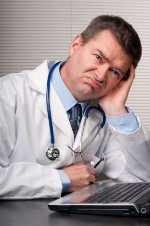 Physician at desk in surgery leans on hand and looks unhappy and bored. Looking  into distance. Humor.