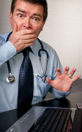 responds: Physician at desk in surgery responds with shock at a patients remarks. Slightly humorous. Stock Photo