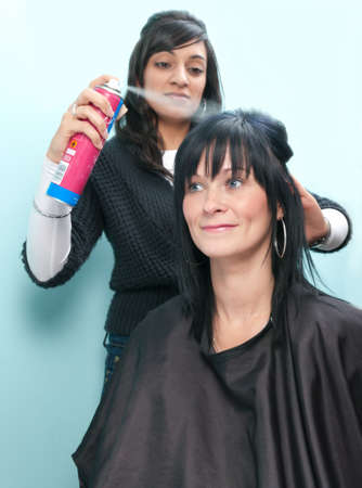 hairspray: Beautiful young woman receives hairspray from attractive Indian hair stylist Stock Photo