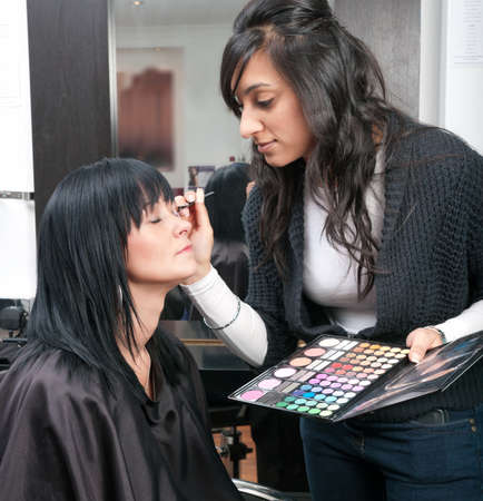 Beautiful young woman receives beauty treatment from attractive Indian beautician.
