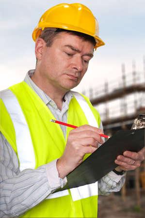 Voorman op bouw plaats controleert details over een klembord.