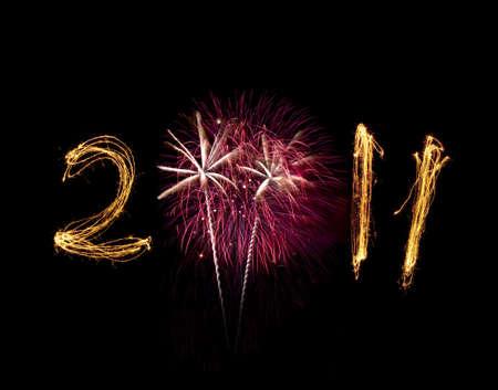 Rosa y blanco de la explosi�n de fuegos artificiales con 2011 escrito con sparklers iluminados. Podr�a utilizarse para a�o nuevo y cuatro de julio. Espacio para la copia de p�ster. Explosi�n reemplaza a cero. Aislados en negro.  Foto de archivo