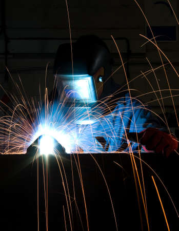 Arc welding in manufacturing plant with copy space at bottom.