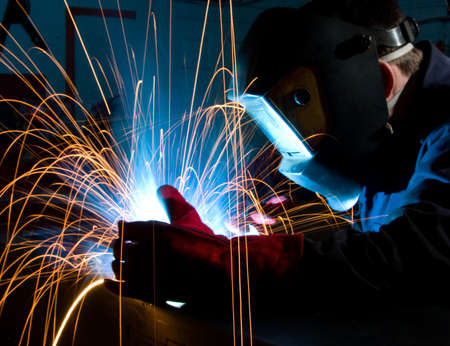 fabrication: Arc welding in manufacturing plant. Close up with red glove. Stock Photo