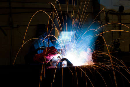 Arc welding in manufacturing plant with flying sparks