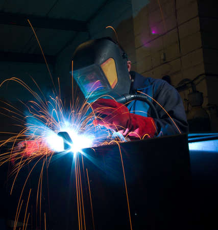 obscured: Arc welding in manufacturing plant. Sparks fly. Copy space.