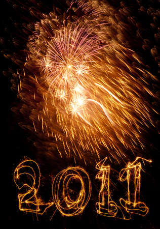 written date: Year 2011 written in sparklers below golden fireworks display. Use for celebrations like New Years, 4th July, Bastille Day. Stock Photo