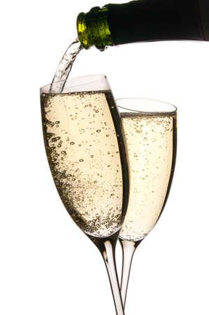 Dos vasos clink en brindis como se vierte el vino espumoso. Burbujas en el l�quido dorado. Aislados en blanco. Copiar el espacio.