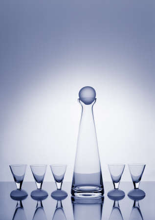 organised group: Modern, slim decanter and five glasses toned blue and backlit with a halo and plenty of copy space.