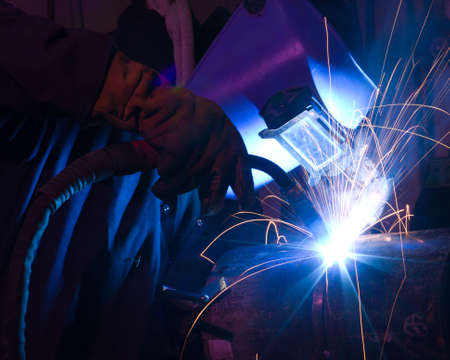 kaynakçı: Welder uses torch to make sparks during manufacture of metal equipment.