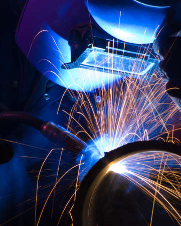 welder uses torch to make sparks during manufacture of metal equipment. Stock Photo