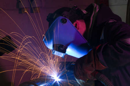 Soldador utiliza la antorcha para hacer chispas durante la fabricaci�n de equipos de metal. Foto de archivo