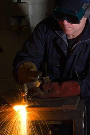 Welder uses torch to make sparks during removal of weld from metal equipment.