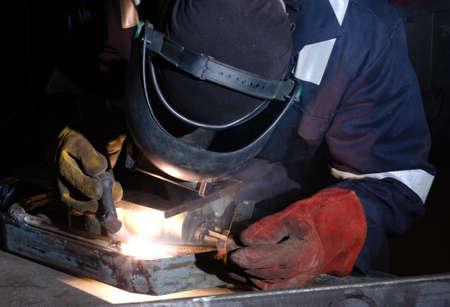 Soldador TIG utiliza la antorcha para hacer chispas durante la fabricaci�n de equipos de metal. Foto de archivo