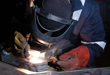 TIG welder uses torch to make sparks during manufacture of metal equipment. photo