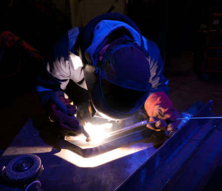Blue-lit TIG welder working closely on metal construction. Copy space.