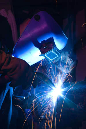 Welder uses torch to make sparks during manufacture of metal tube. Stock Photo