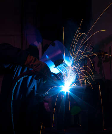 mig: Welder uses torch to make sparks during manufacture of metal equipment.